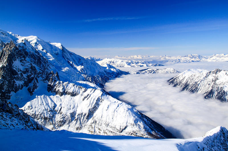 Fog flows in a snowy valley between mountains stock image