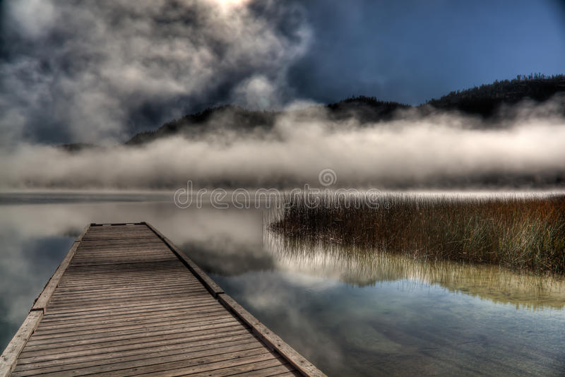 Fog Hovering Over Lake. Its a fairly clear day at the lake, but the morning fog is still lingering and hovering above the water on the lake giving it a royalty free stock photos