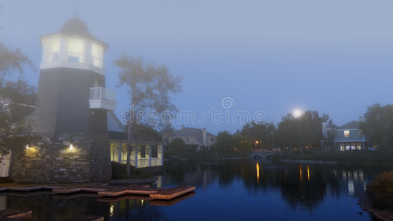Fog on the Lake. Dreamy dusk on a lake with a moon rising over the trees and the lights reflecting on the water in orange and yellow