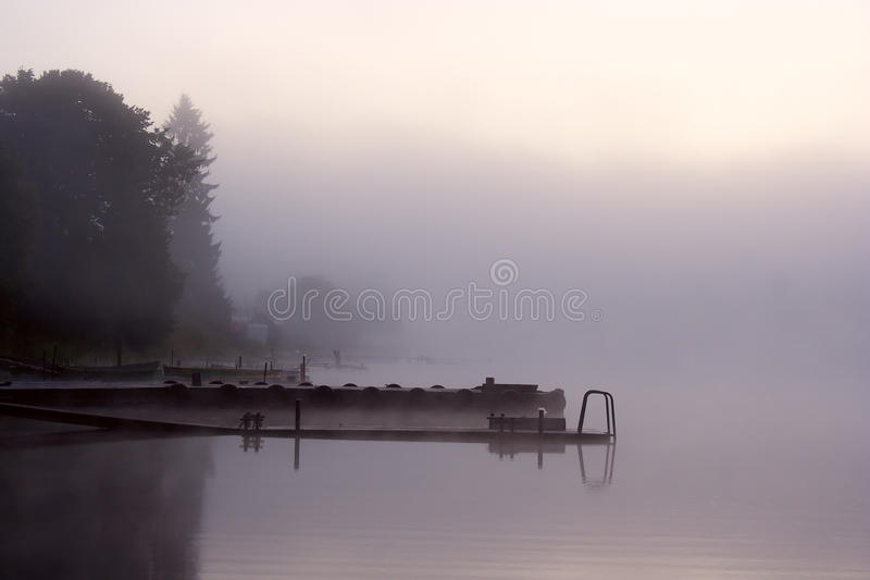 Fog lake trees moorage. Morning nature scene (landscape): fog (mist) reflected in the water surface along with trees and moorage (quay, berth, wharf). The stock image