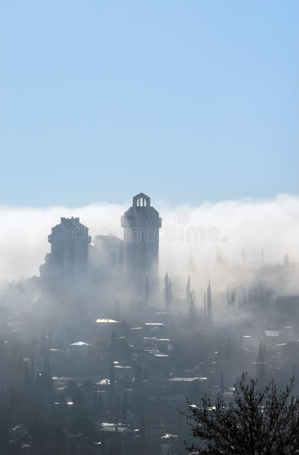 Fog over the city. City is covered with mist in sunlight and blu royalty free stock image