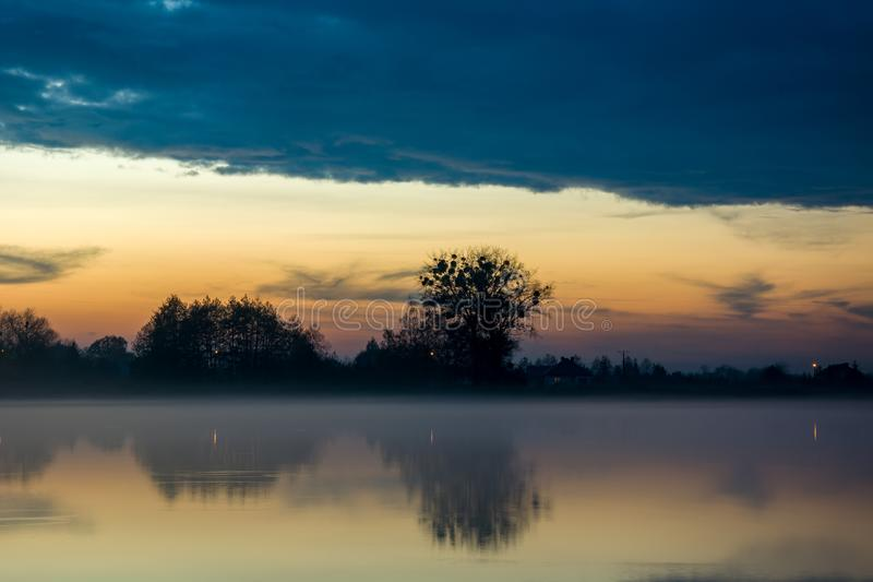 Fog over the lake and cloud in the sky. Fog over the lake, trees on the horizon and blue cloud in the sky stock photography