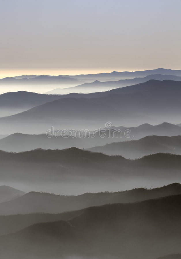 Fog over the mountains. Far away view of mountain covered by fog stock images