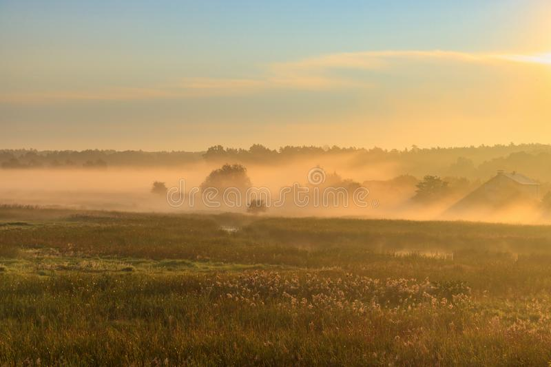 Fog over village houses in orange rays of rising sun in autumn morning. Nature landscape stock photography