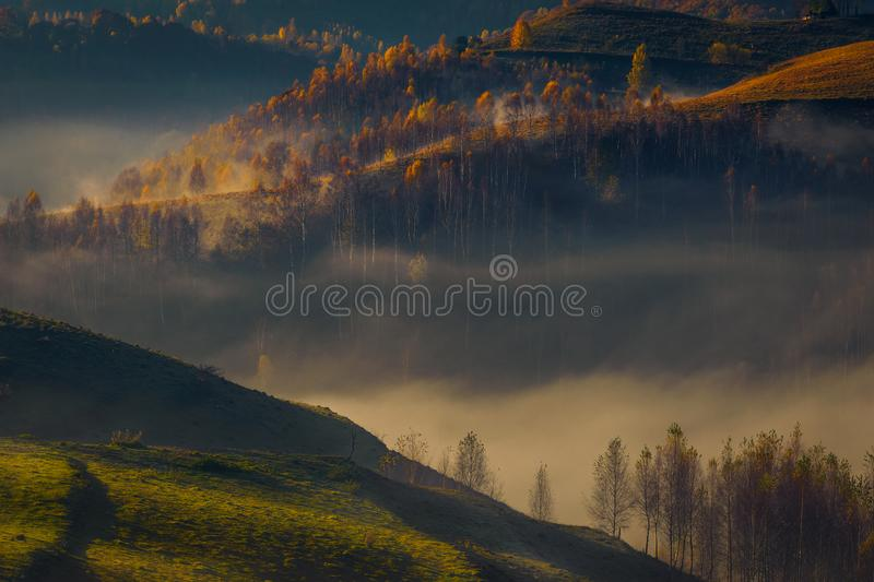 Fog passing through a valley after sunrise with beautiful autumn colored forest stock photo