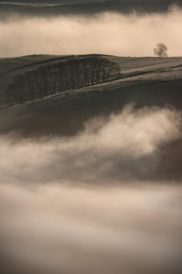 Fog - Peak District Landscape. Cow Low and Peveril Wood from Mam Tor. A cloud inversion fills the bottom of Winnats Pass in the foreground and Pindale in the stock images