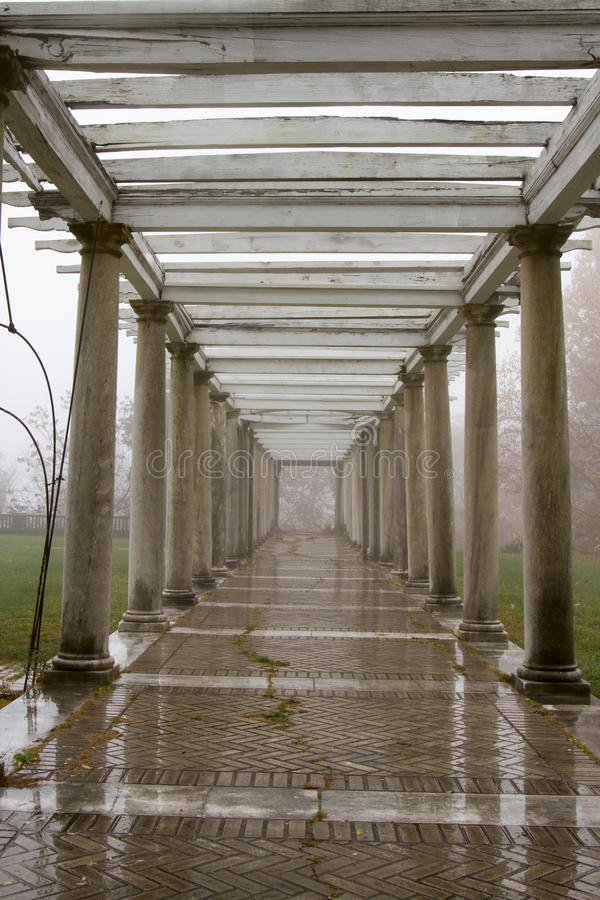 Fog and rain in garden ruins. Breezeway in garden on foggy and rainy day royalty free stock images
