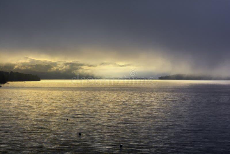 Fog rising over the mountain at Sacandaga lake stock photography