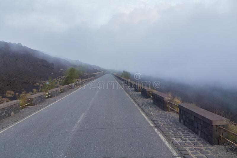 Fog on the road that leads to Etna stock photo