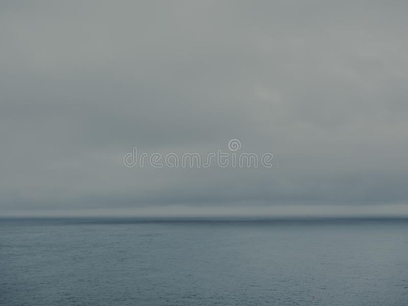 Fog rolling in over seascape on overcast day royalty free stock photo