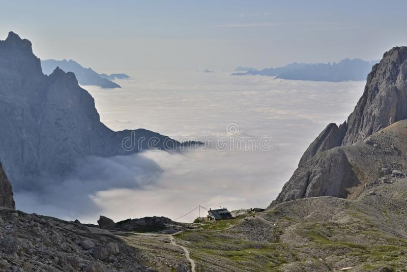 Fog rolling up in a valley between rocks in mountains - mountain chalet is just above the fog. royalty free stock images