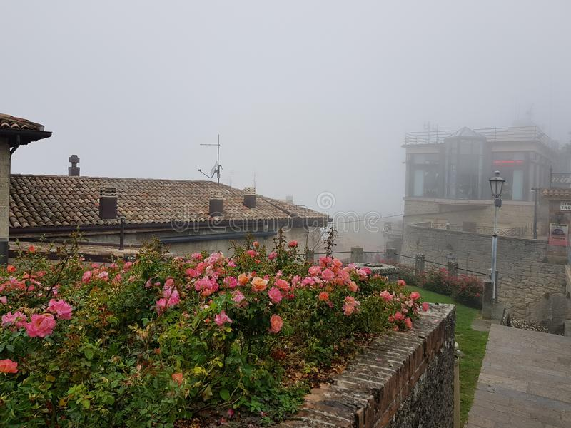 Fog in San-Marino. Flowers, city, architecture royalty free stock photography