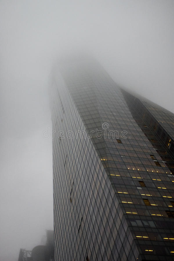 Fog Scraper. Fog covering the top of a sky scraper royalty free stock image