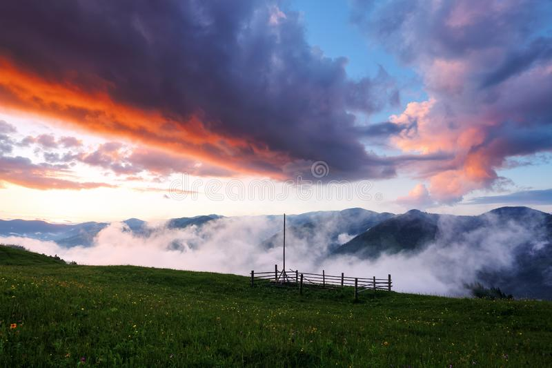 Fog spreads across the valley. Landscape with beautiful mountains. Panorama with interesting sunrise enlightens surroundings. royalty free stock photo