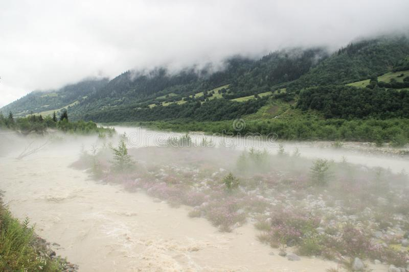 Fog spreads over the river and mountains in the early morning in Svaneti royalty free stock image