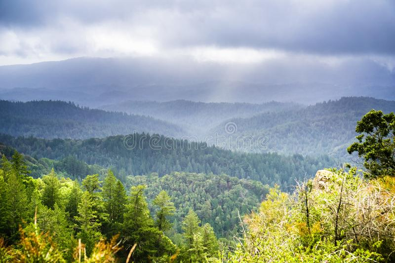Fog and storm clouds covering the green hills and valleys of Santa Cruz mountains. As seen from Castle Rock State Park, San Francisco bay area, California stock images