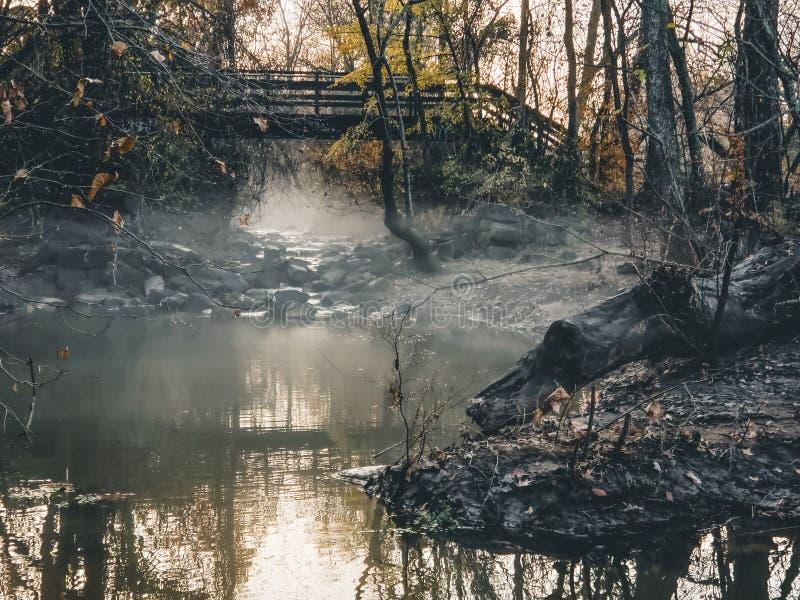 Fog on a stream and bridge at sunset. stock photos