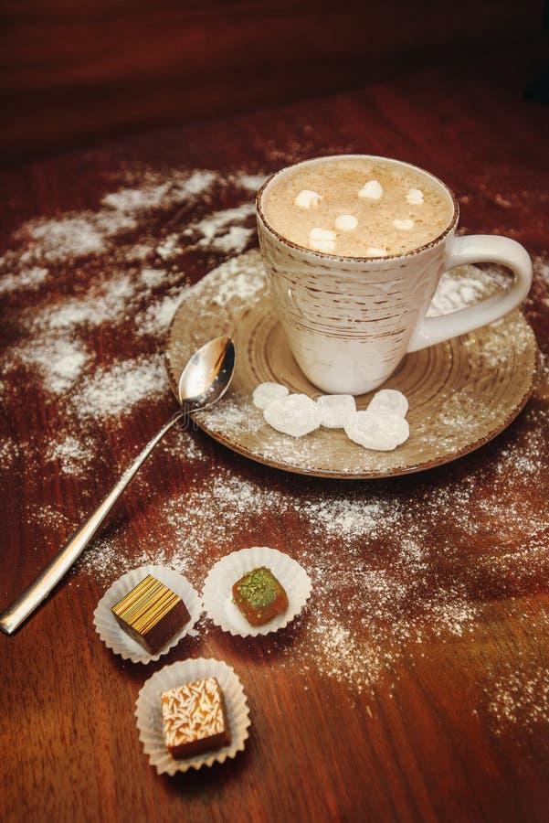 Foggi a coppa il cacao caldo con le caramelle gommosa e molle, biscotti su uno scrittorio con la polvere dello zucchero per la fe immagine stock