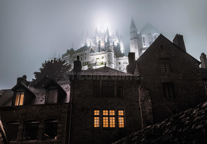 Foggy abbey of Saint Michel illuminated in the night royalty free stock photos
