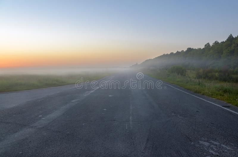 Adverse driving conditions.Fog over the empty asphalt road. Foggy autumn landscape at sunrise stock photos