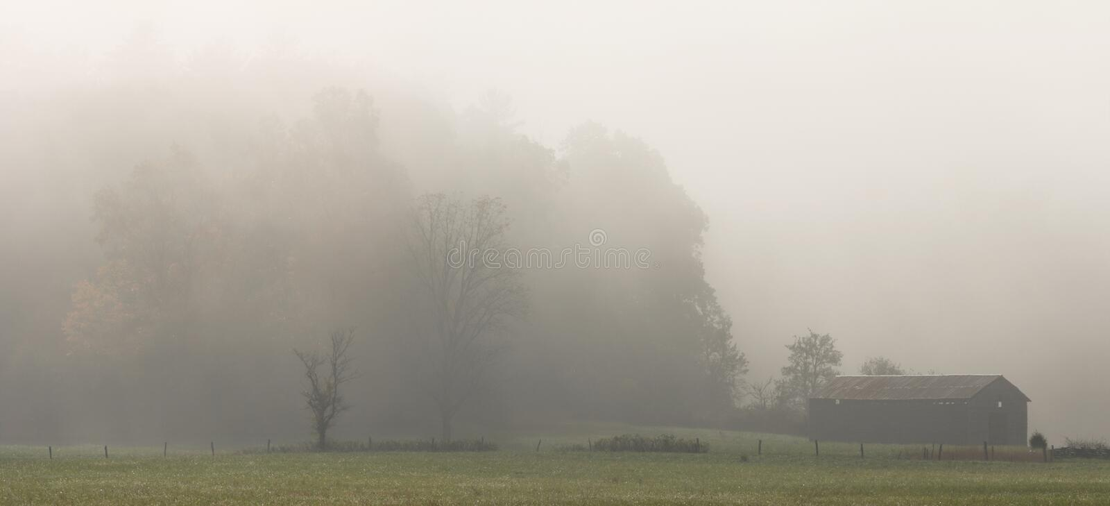 Foggy Barn in Cades Cove. A foggy autumn morning in Cades Cove, a valley of the Smoky Mountains Nat. Park, USA. Stitched panorama stock photography