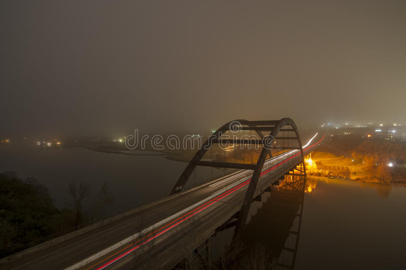 Foggy bridge at night royalty free stock image