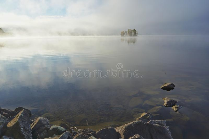 Foggy bright autumn morning on the lake stock photography