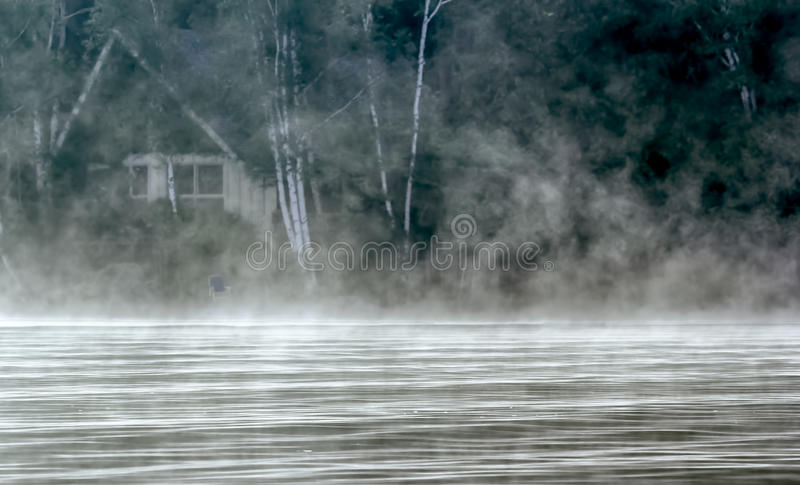 Foggy Cabin in the Woods. A cabin in the woods surrounded by dense fog. This specific cottage has documented ghost sightings stock photography