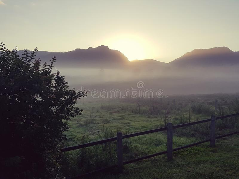 Foggy country sunrise overlooking mountains stock photo