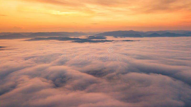 Foggy dawn in mountains. Sea of fog between mountain peaks stock image