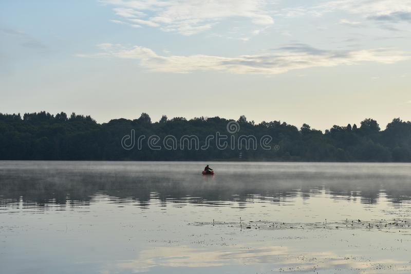 Foggy dawn on the river, a lone fisherman from a boat fishing, forest and clouds reflected. In the water stock photos