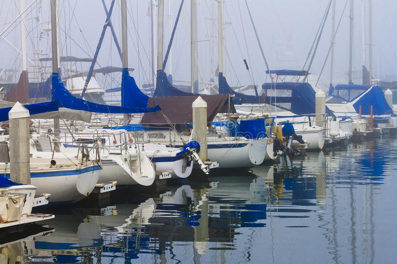 Foggy Harbor. This image is of boats anchored in a very foggy Oceanside, California harbor. This photograph was taken early one winter morning stock photo