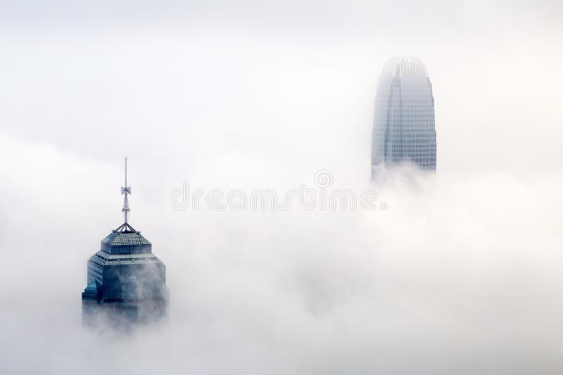 The foggy Hong Kong skyline. HONG KONG - MAR 3. The foggy Hong Kong skyline on Mar 3, 2018. Many buildings are covered when viewed from the Peak. Only the royalty free stock photos