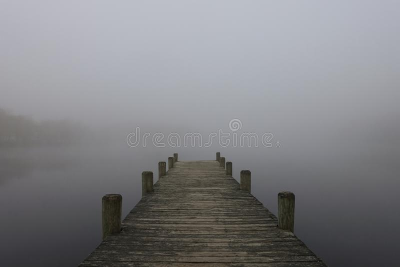 Foggy lake in Lakewood in New Jersey. A pier on a foggy lake in Lakewood, New Jersey royalty free stock photos