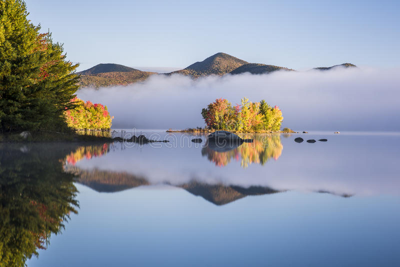 Foggy Lake and Green Mountains - Island with Colorful Trees - Autumn / Fall - Vermont. A foggy view of Chittenden Lake and the Green Mountains looking towards royalty free stock image