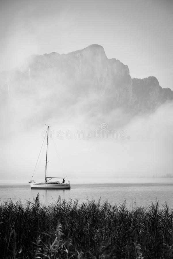 Foggy lake with lonely boat - Mondsee, Austria.  stock photography