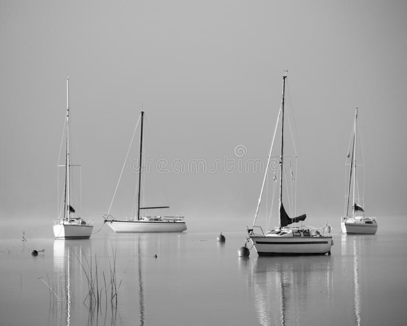 Foggy lake with lonely boats - Mondsee, Austria.  stock images