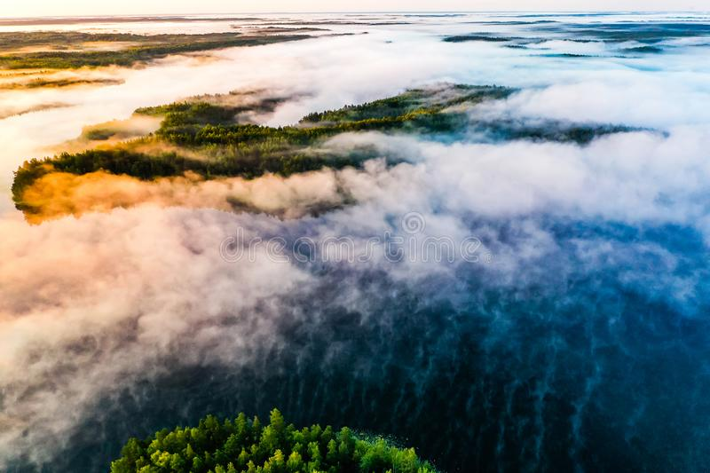 Foggy landscape. Aerial scenery. Blue lakes and green forest view at sunrise. Fresh air concept stock images