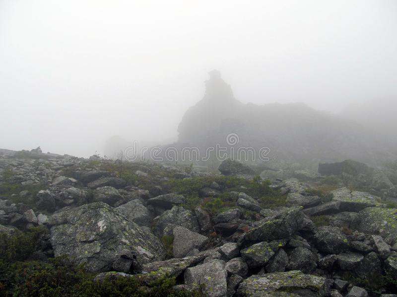 Mountain tundra in a fog. Foggy landscape of a high mountain plateau with boulders and tundra vegetation while in the cloud stock images