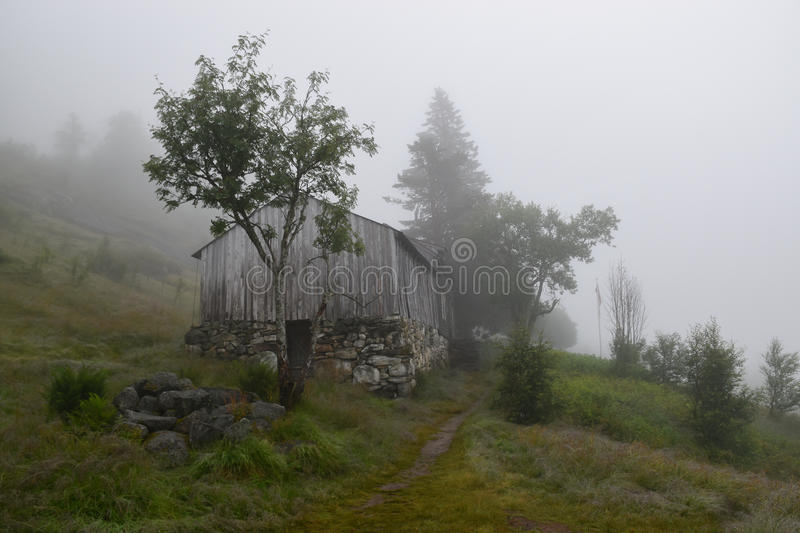 Foggy landscape with mountain farm in Eidfjord, Norway royalty free stock images