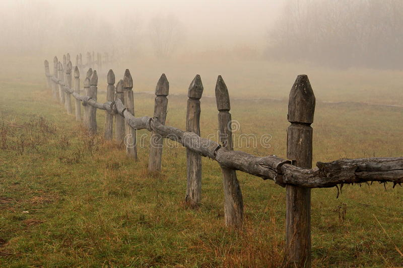 Foggy landscape. Old rustic fence on a foggy morning royalty free stock photos