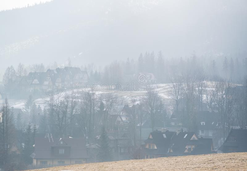Foggy morning mist over mountain valley with rural farm house buildings stock image