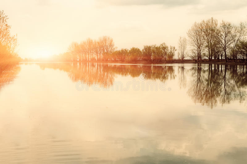 Foggy morning sunny landscape with trees and clouds reflections in river.  stock images