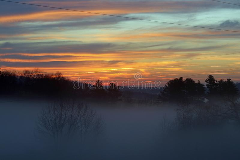 Foggy morning sunrise and clouds. A foggy morning sunrise with orange and blue skies royalty free stock photos