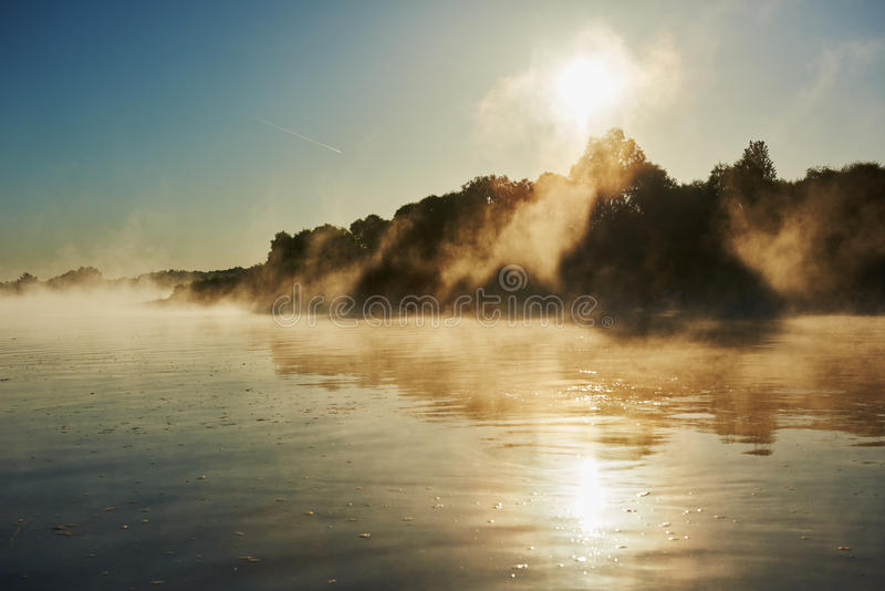 Foggy morning sunrise over river. Picturesque reflective landscape of foggy misty sunrise over river in summer stock images
