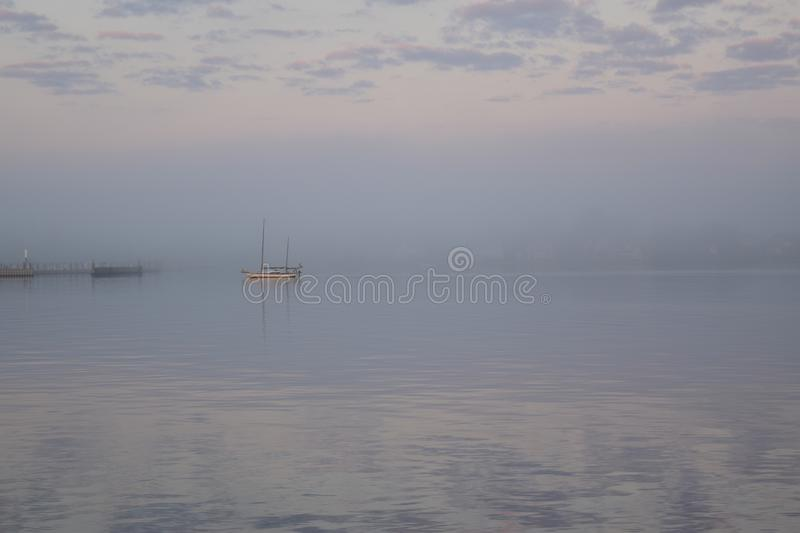 Foggy Morning on the Water. A boat anchored in the water is surrounded by fog on the Elizabeth River one chilly spring morning. View from Town Point Park in royalty free stock image