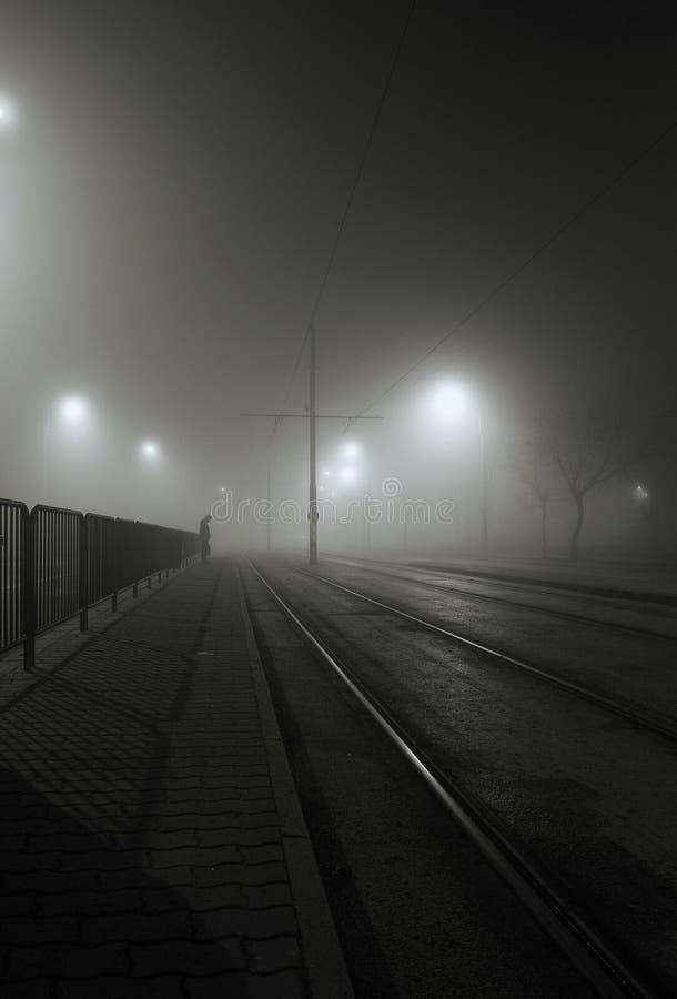 Foggy night. On the street, man waiting along the railroad streetcar tracks stock photography