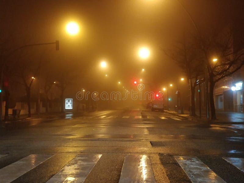 Foggy night with blurred street lights. Illumination, winter, nature, quiet, darkness, urban, mystery, way, horror, season, city, asphalt, town, silent, black stock image