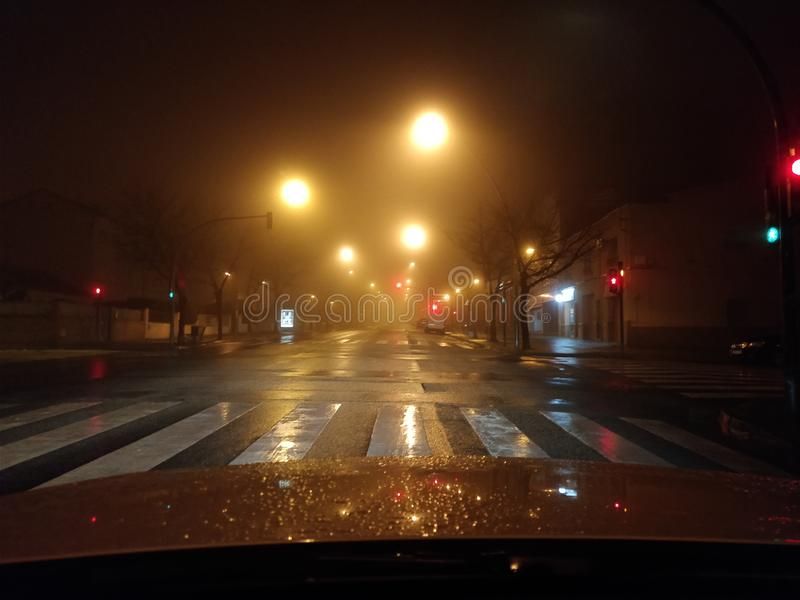 Foggy night with blurred street lights stock photography