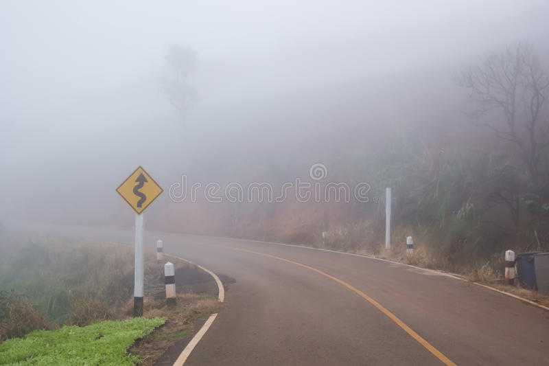 Foggy road. With curve sign royalty free stock images